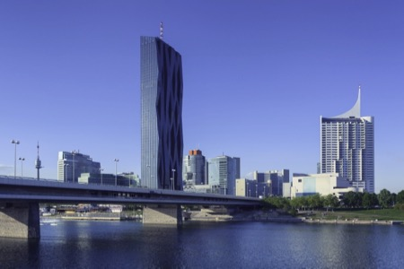 Vienna city by the Danube river. The DC tower, the tallest building in Austria at 250 metres, rises above the other buildings.